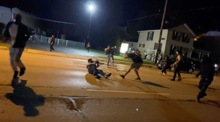 De man rechts wordt in zijn borst geschoten tijdens rellen in Kenosha die volgden op het neerschieten van de zwarte Jacob Blake door een witte agent. Beeld Getty