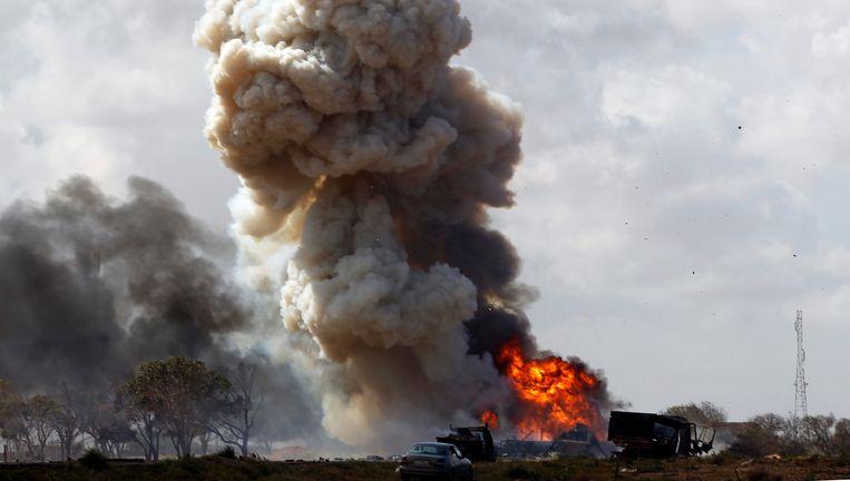 Exploderende voertuigen, die behoren aan troepen van Kadhafi, exploderen na een luchtaanval. Beeld reuters