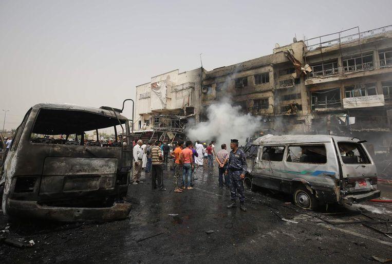 Politie en burgers inspecteren de ravage na de aanslag in de wijk al-Jadeeda. Beeld afp