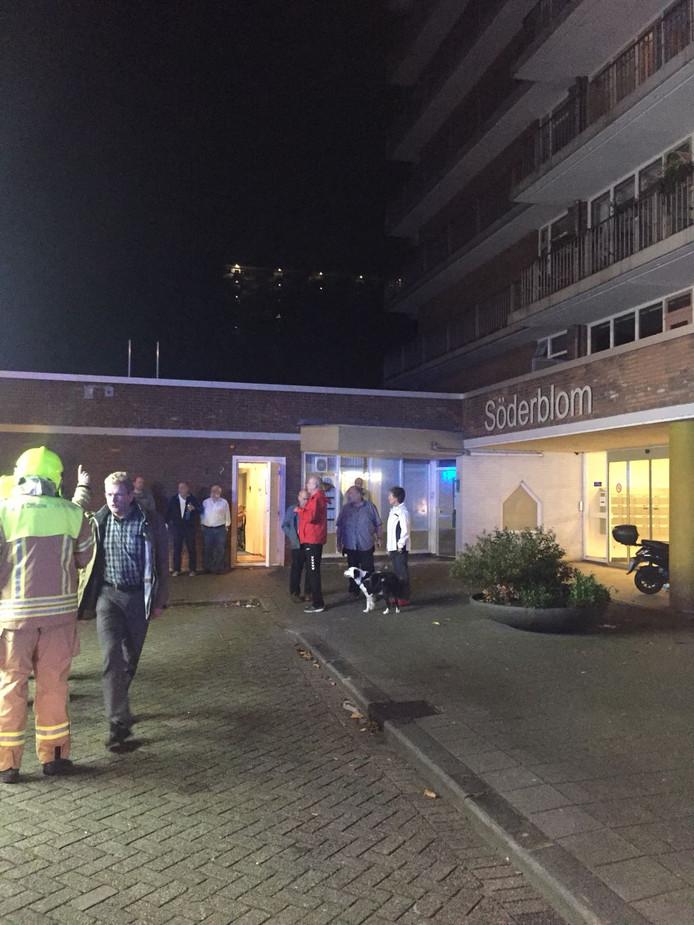 Mensen worden opgevangen in een zaaltje nabij de flat.