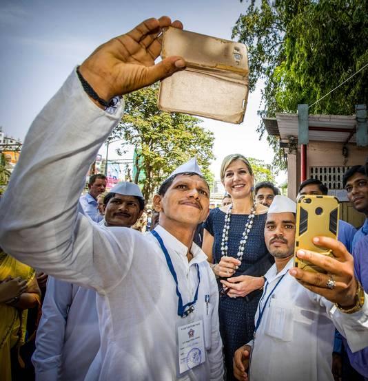 Twee maaltijdbezorgers maken een selfie met onze koningin Máxima