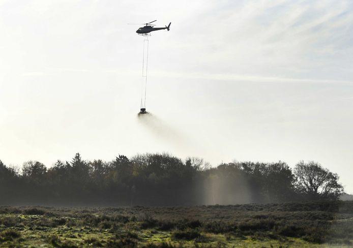 Een helikopter strooit schelpgruis uit voor het bekalkingsproject van de heide en bossen van De Ginkel. De kalk uit het schelpgruis maakt het bos- en heidegebied minder zuur.