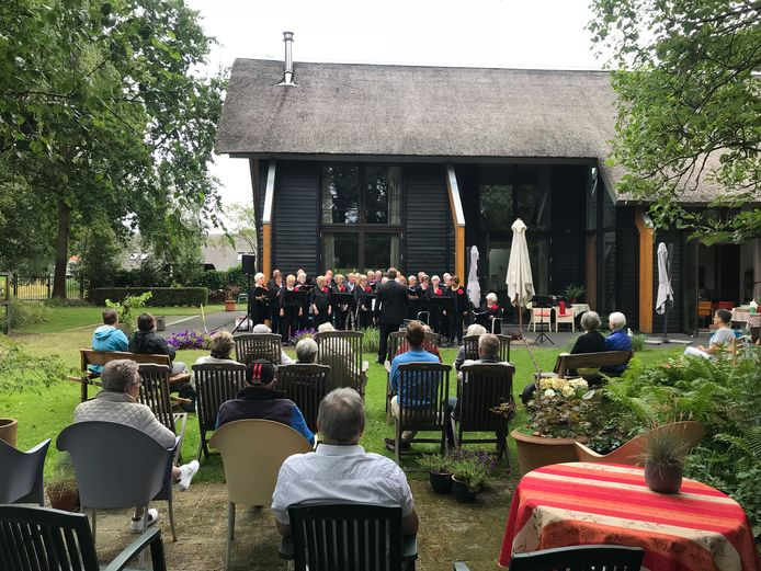 In de tuin van Kees en Jeanny de Goey luistert het publiek naar het optreden van het Ambiancekoor.