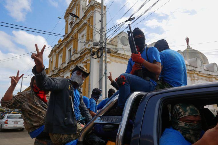 Gewapende aanhangers van de regering vieren de verovering van de wijk Masaya. Het centrum van het verzet tegen de regering van Daniel Ortega is nu weer in handen van de president. Beeld AP