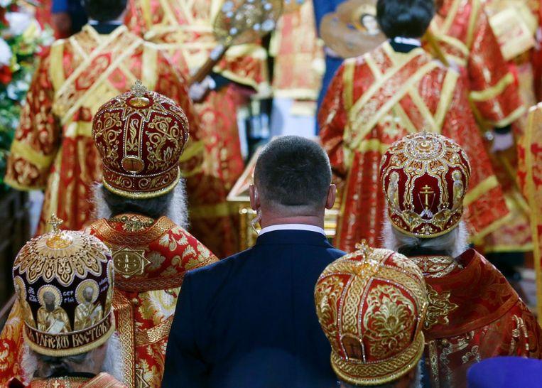 Een beveiliger bidt te midden van bischoppen in de Christus Verlosserskathedraal. Beeld Sergei Chirikov / EPA