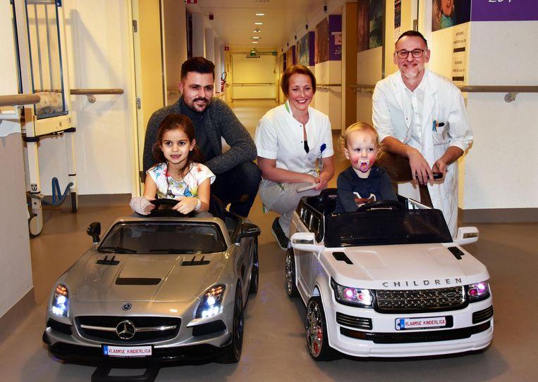 Joeri Verbraeken van de Vlaamse Kinderliga, Ann Van de Bossche, hoofdverpleegster kinderafdeling en kinderarts dr Luc Pattyn. In de auto's Britt en Flor.