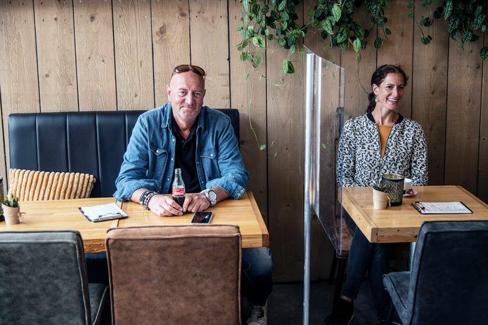 Mike Neuij met zijn vrouw Sharon in de lunchzaak, van elkaar afgeschermd met mobiel plexiglas paneel. Hij zit aan een tafel voor maximaal vier personen uit één gezin.