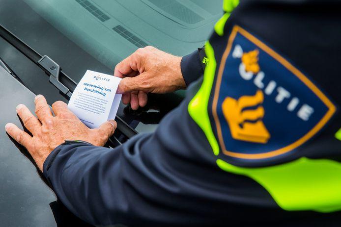 2015-07-13 17:08:49 APELDOORN - Een politieagent plaats een label onder een ruitenwissen bij een parkeerovertreding. De politie gaat digitaal bekeuren en vervangt daarbij de papieren bekeuring voor een label. ANP VINCENT JANNINK