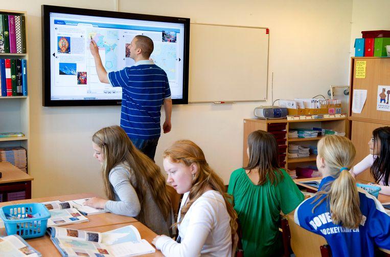 Een leraar geeft uitleg aan de klas op een digitaal schoolbord. Beeld Lex van Lieshout, ANP