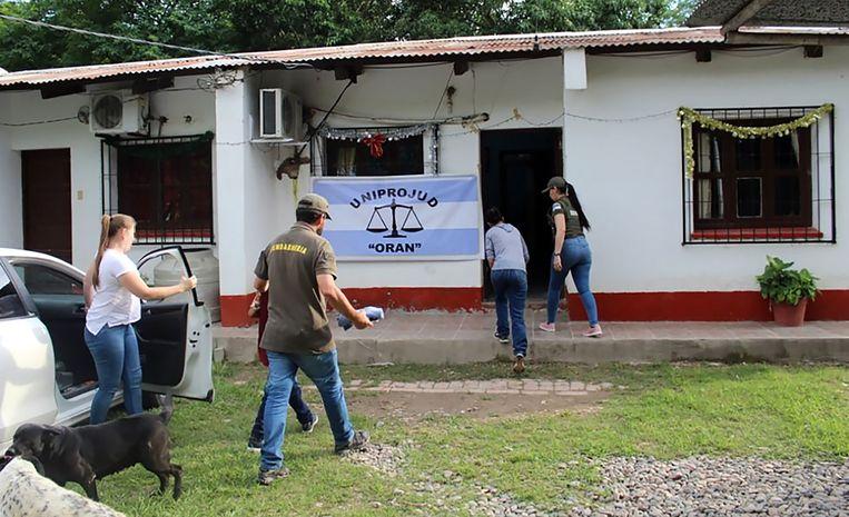 De vrouw (tweede van rechts) en haar zoontje worden door de politie begeleid terwijl ze haar ouderlijk huis binnengaan.