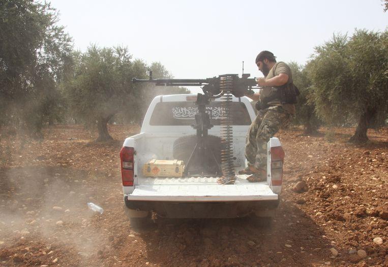 Een lid van de Syrische Sultan Murad Brigade met een automatisch wapen tijdens een gevecht met IS in de buurt van Aleppo (september 2015). Beeld Getty Images
