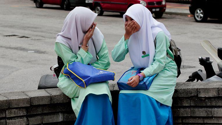 Twee jonge meisjes op straat in Kuala Lumpur. Beeld AP