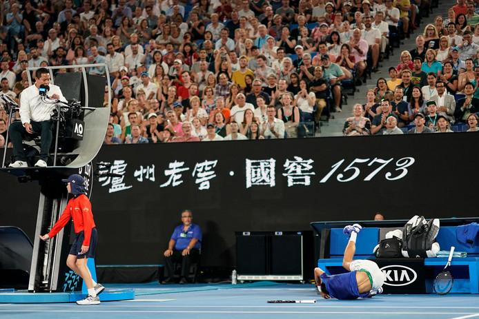 Novak Djokovic op de grond na een uiterste poging om de bal nog te halen.
