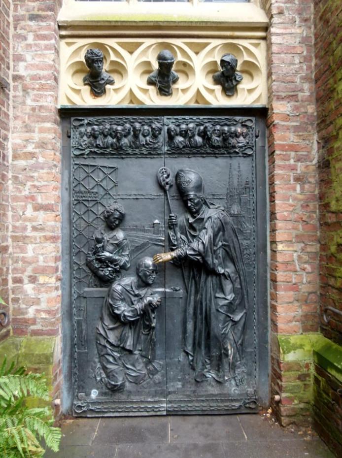Op een bronzen deur in de basiliek van Kevelaer is de wijding van Leisner in Dauchau afgebeeld.