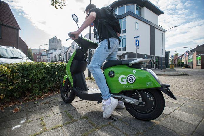 Een student staat op het punt weg te rijden met een felgroene e-scooter van Go Sharing in het centrum van oosterhout. De reacties op de scooters zijn wisselend.