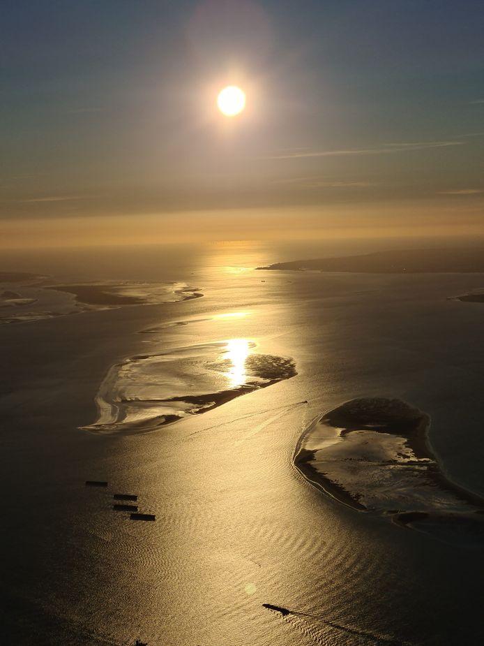 De avondzon blikkert in de Westerschelde, die er vanuit een heteluchtballon nietiger uitziet dan wij haar kennen vanaf de grond. Kleine scheepjes laveren tussen de zandbanken door. Walcheren lijkt inderdaad een eiland.