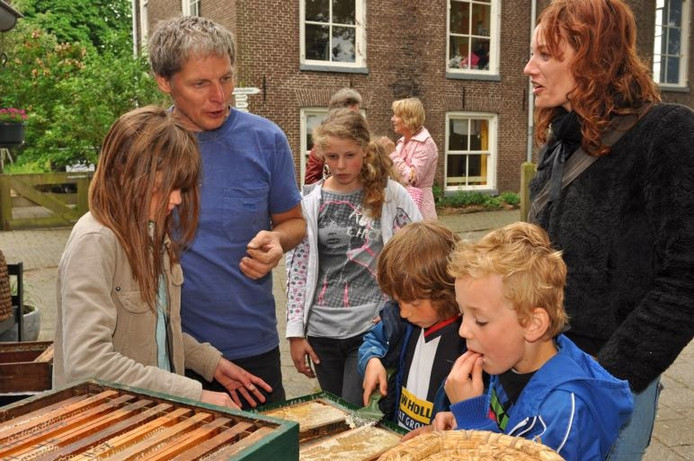 Jeroen den Boer (links) laat bezoekers van De Klooienberg zien hoe het oogsten van honing in z'n werk gaat. Sinds drie jaar is hij imker op de wijkboerderij. foto Suzanne Breman