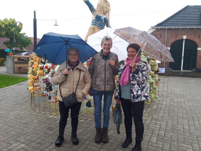 Antje Bruggeman, Janke ten Hove en Nel Roomer bekijken de kunst van onder hun paraplu's.