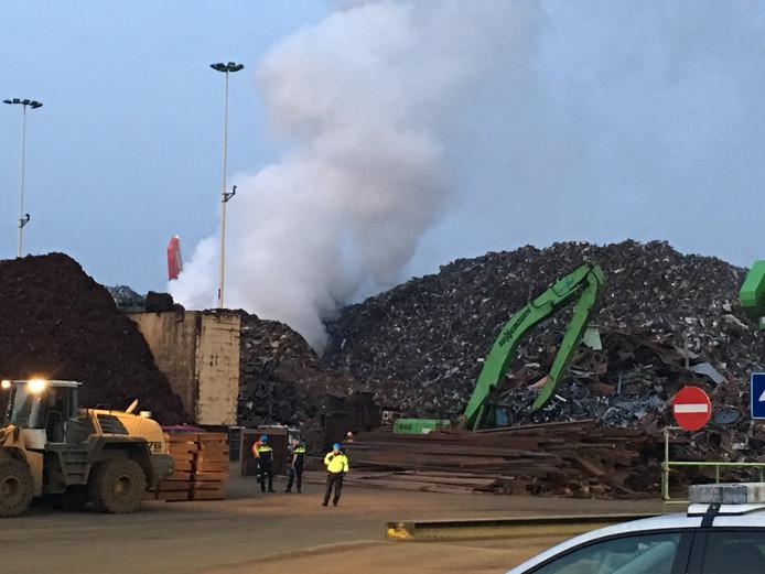 De brand woedt in een enorme berg metaalafval