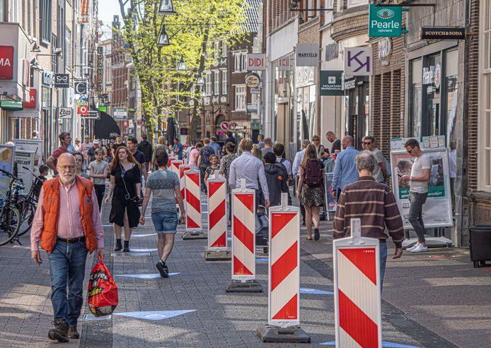 Drukte in het centrum van Zwolle, waar men een scheiding in het midden heeft aangebracht om zo de stromen mensen in goede banen te leiden.