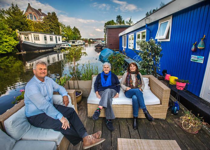 Willem Minderhout, buurvrouw Wil en zijn partner Sophie (r) op hun woonark.