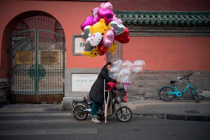 Een vrouw verkoopt ballonnen in Beijing vanaf haar brommertje. Foto Fred Dufour
