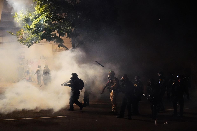 Zwaarbewapende federale agenten drijven met traangas een betoging in Portland uiteen.   Beeld Getty Images