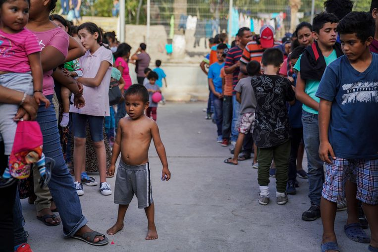 Migranten die in een tentenkamp in Mexico verblijven in afwachting van hun asielverblijf schuiven aan voor voedsel.