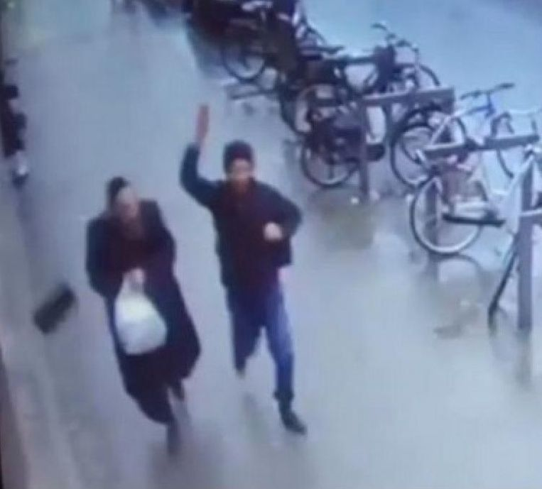 Op camerabeelden is te zien hoe de vluchteling het hoofddeksel van een Joodse man wegslaat.