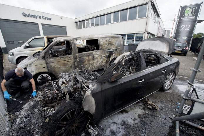Een rechercheur onderzoekt de auto's van Quintys' Crew die de afgelopen nacht in vlammen opgingen