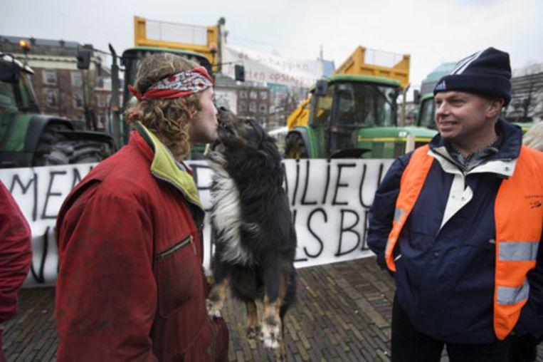 Boeren demonstreren dinsdag op het Plein in Den Haag tegen het beleid van de regering inzake het mestbeleid. De boeren overhandigden een manifest aan parlementariërs, waarin ze pleiten voor het afschaffen van de zogeheten productschappen. Een hond geeft een kus aan zijn baasje. (Martijn Beekman - de Volkskrant) Beeld
