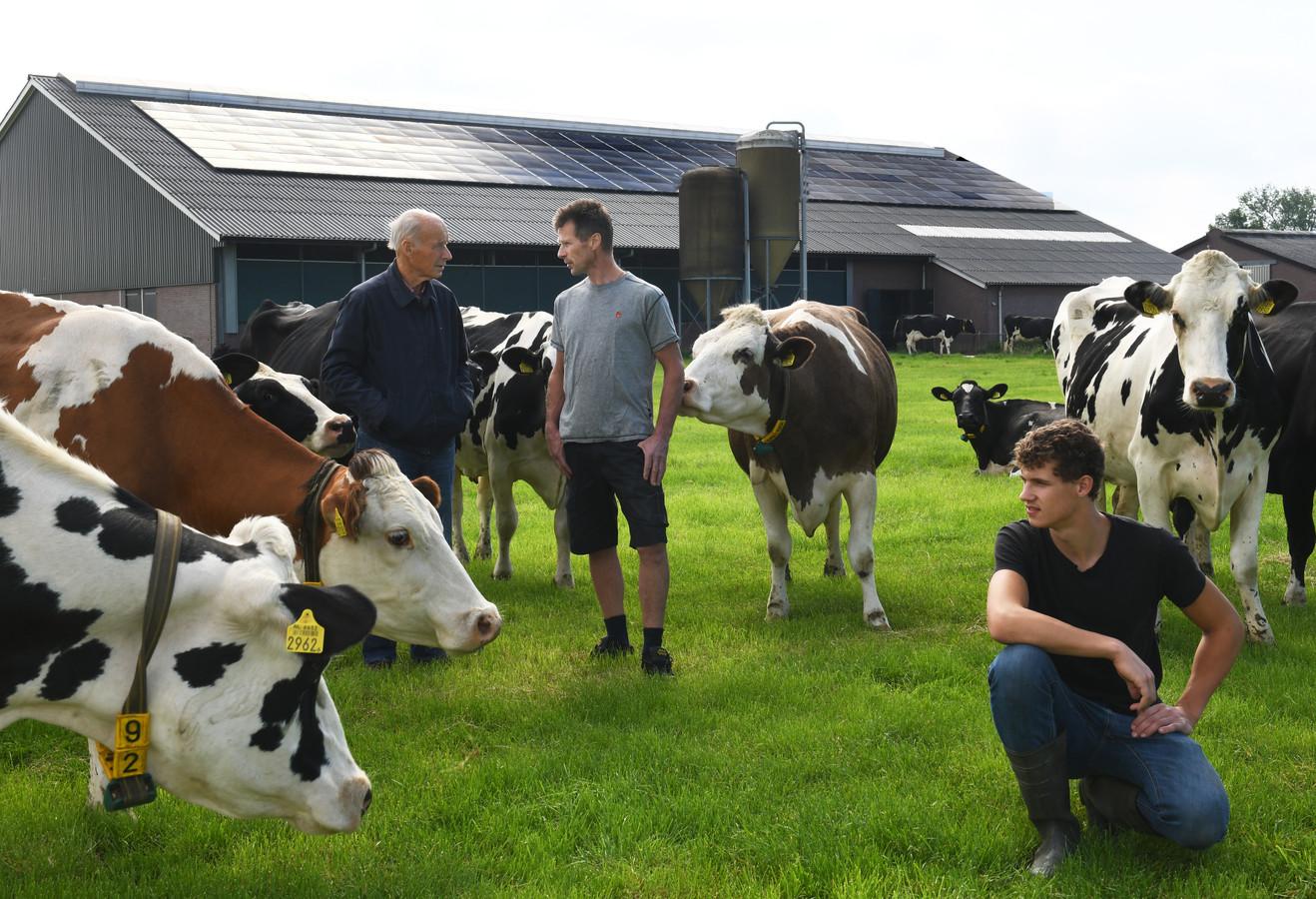 Landschapsbeschermer Wim van der Putten (links) op het melkveebedrijf van Dick Vink (rechts) in Lopik, die al een staldak vol zonnepanelen heeft. Op de voorgrond oudste zoon en bedrijfsopvolger Stefan.