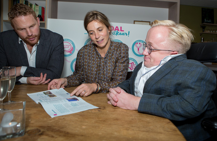 Gedeputeerde Roy de Witte, minister van Gehandicaptenzaken Rick Brink (r) en directeur Esther van der Kooij van de Imminkhoeve koesteren de brochure 'Zorgeloos genieten in het Vechtdal'.