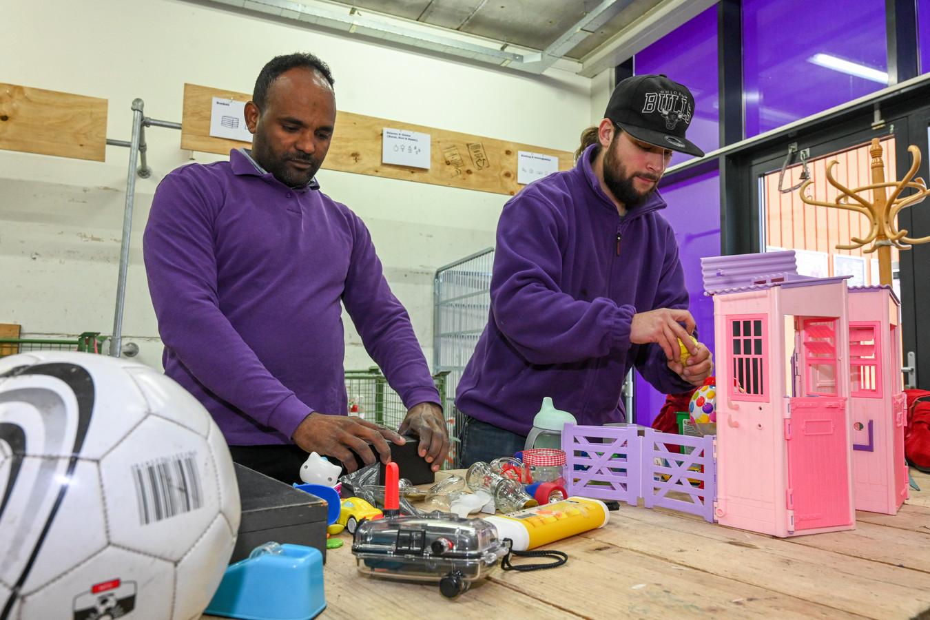 Bij Het Goed in Harderwijk zoeken Gere Mebrhtu (links) en Rene Bruin de nieuw binnengebrachte spullen uit. Er zit veel kinderspeelgoed bij.