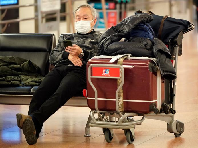 Een reiziger op het vliegveld van Tokio draagt een mondkapje om besmetting te voorkomen.