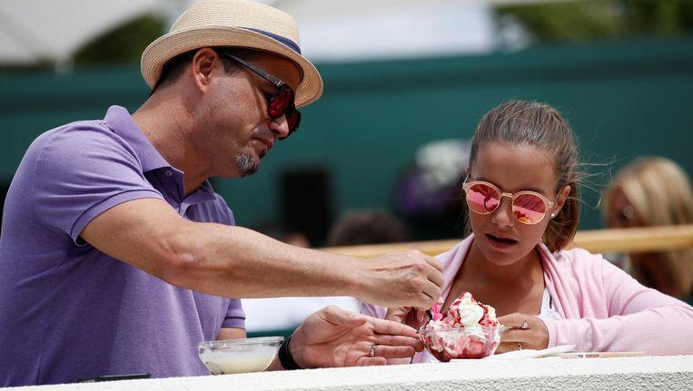 Bezoekers van Wimbledon eten aardbeien met slagroom. Beeld reuters