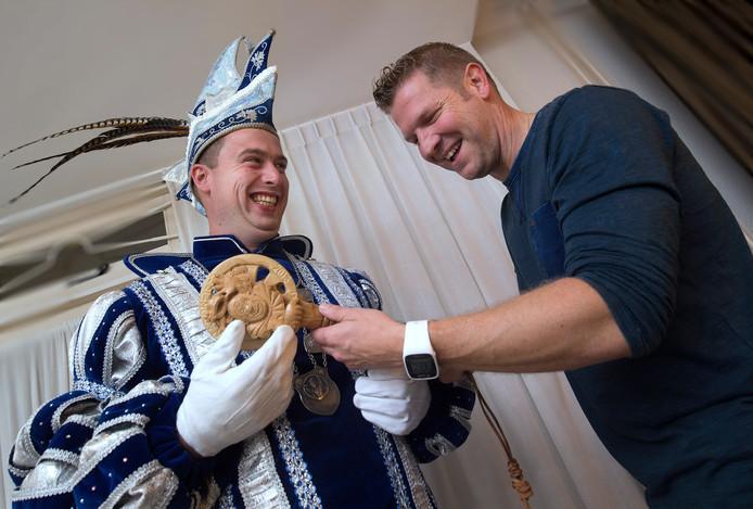 Prins Thijs (links) ontvangt de uit hout gesneden scepter van oud-prins Roland (rechts).