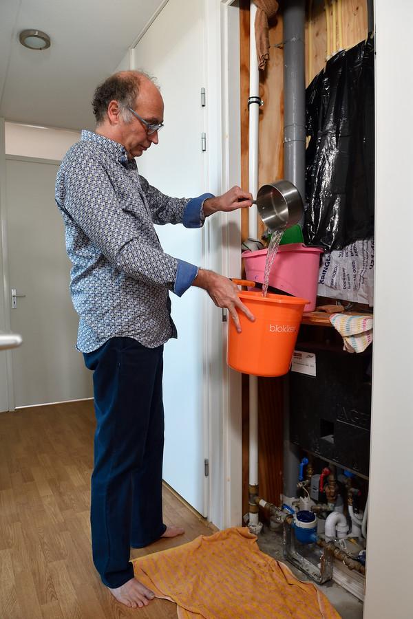 Bewoner Henkjan Schriemer heeft een ingenieuze manier gevonden om zijn meterkast enigszins droog te houden. Via een doek sijpelt het water in een emmer, waarna het kan worden afgevoerd.