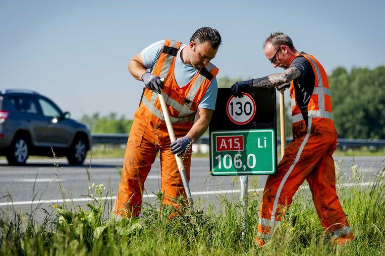Medewerkers van Rijkswaterstaat plaatsen hectometerbordjes met snelheidsaanduiding langs de A15 bij Herwijnen, 2014. Beeld ANP