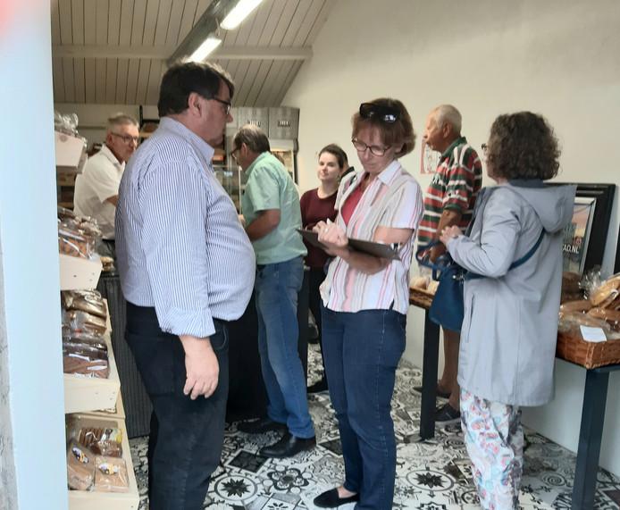 Voorzitter Jan Paul Loeff (links) van de stadsraad Veere haalt handtekeningen op voor de petitie in de rij wachtenden in de bakkerswinkel in de opslagplaats van bakker Bliek aan de Rijkendijk, grenzend aan het Oranjeplein. De Stadsraad verzamelde  512 steunbetuigingen.