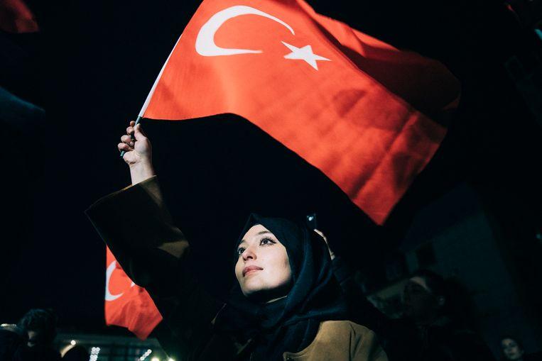 De Turkse vlag wappert tijdens de samenkomst van duizenden mensen. Beeld null