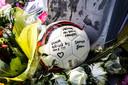 Een bal bij met opschrift ligt tussen de bloemen op de ongevalslocatie langs de A1.