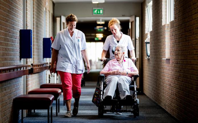 Een bewoonster van een zorginstelling met verpleegsters
