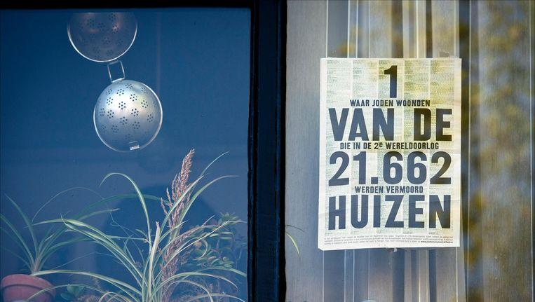 Raamposters op een woonhuis aan de Keizersgracht refereren aan de voormalige Joodse bewoners. Beeld anp