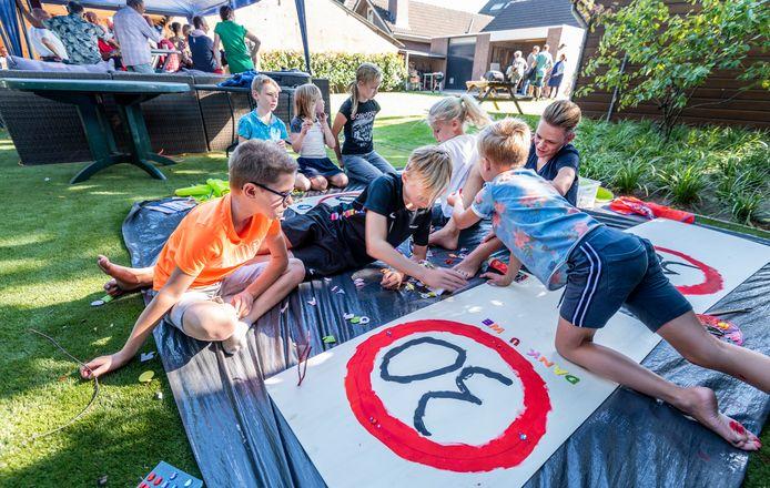 Kinderen maken tijdens de buurtactie eigen waarschuwingsborden voor de Oudedijk in Odiliapeel.