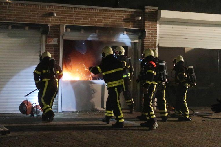 Brandweermannen maandagavond aan het werk bij de garagebox in Breda waar de 49-jarige man in brand was gestoken. Beeld null