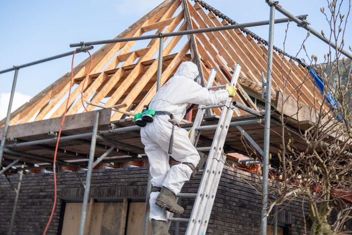 Een man in een beschermend pak is bezig met het verwijderen van asbest uit een dak.