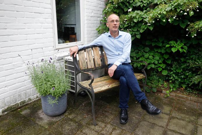 Nijmegenaar Puk van Meegeren bij zijn achter het bankje weggestopte warmtepomp.