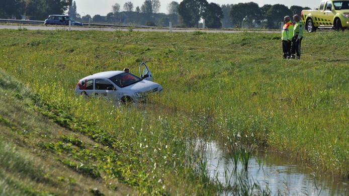 Hulpverleners bekijken de situatie nadat een auto op de A4 van het talud is gereden.