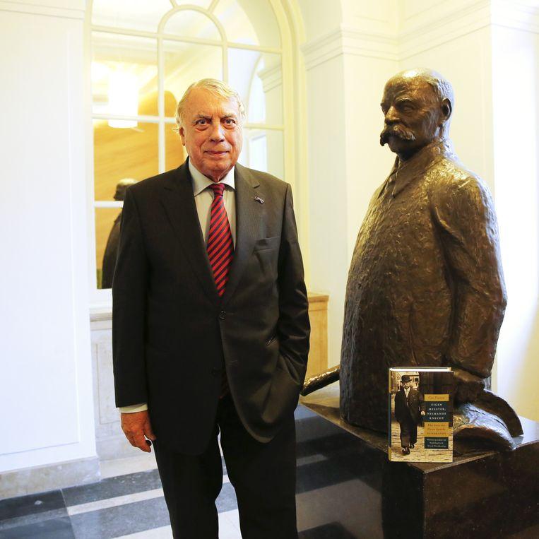 Biograaf Cees Fasseur, schrijver van de biografie 'Eigen meester, niemands knecht' over het leven van voormalig minister-president Gerbrandy, poseert naast het standbeeld van Gerbrandy. Beeld anp